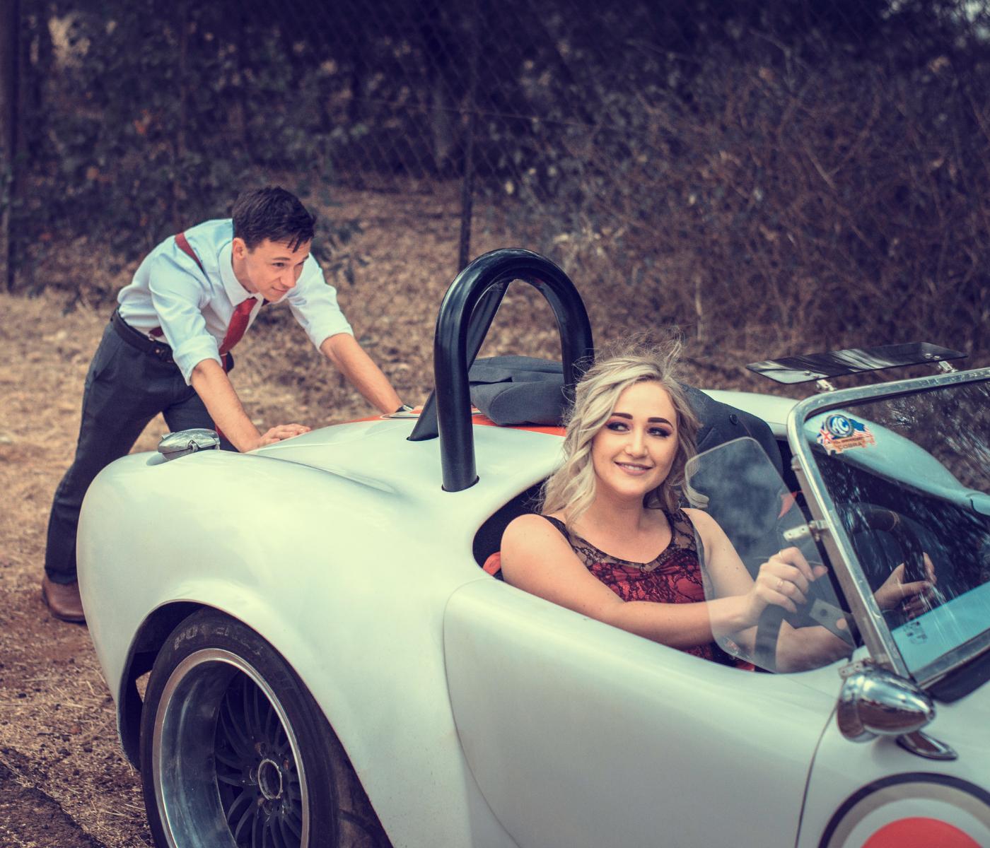 man pushing a car with women inside